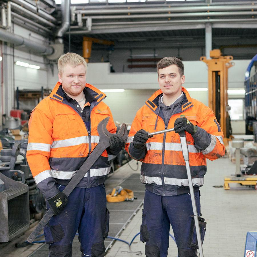 Zwei junge Männer stehen mit Werkzeug in der Hand in einer Werkstatt für eine Recruiting kampagne vor der Kamera