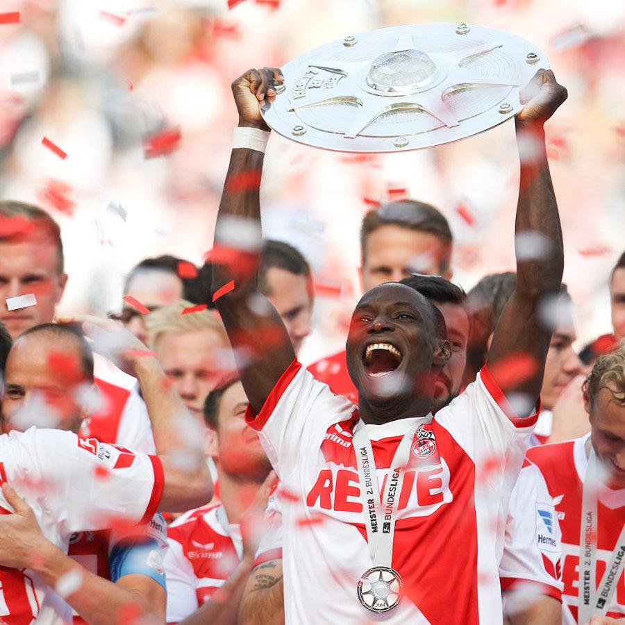 Ein Fußballspieler hält einen Pokal in die Luft und freut sich